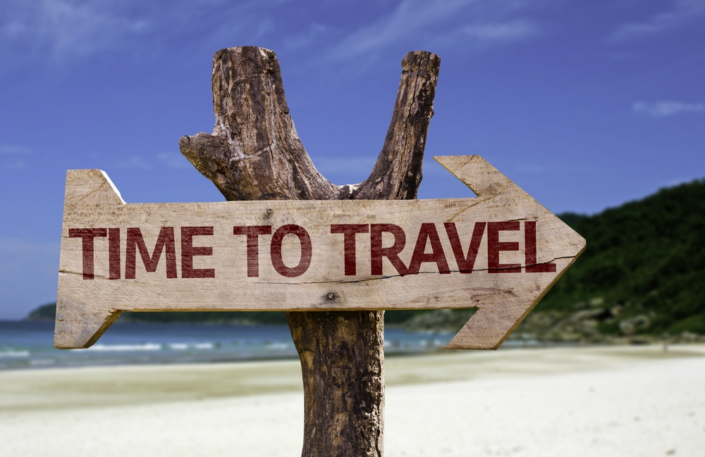 Time to Travel wooden sign with a beach on background.jpeg